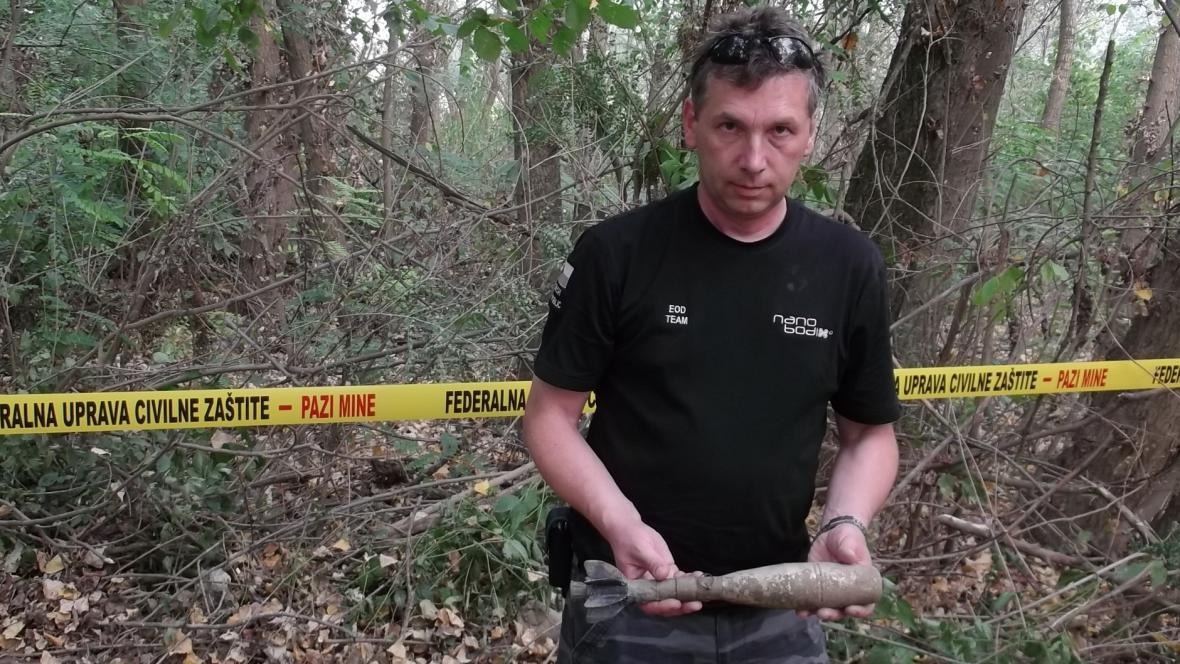 Policista ukazuje nalezenou munici