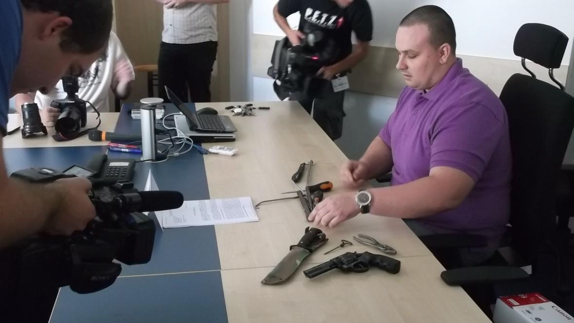 Policista ukazuje recidivistův arzenál