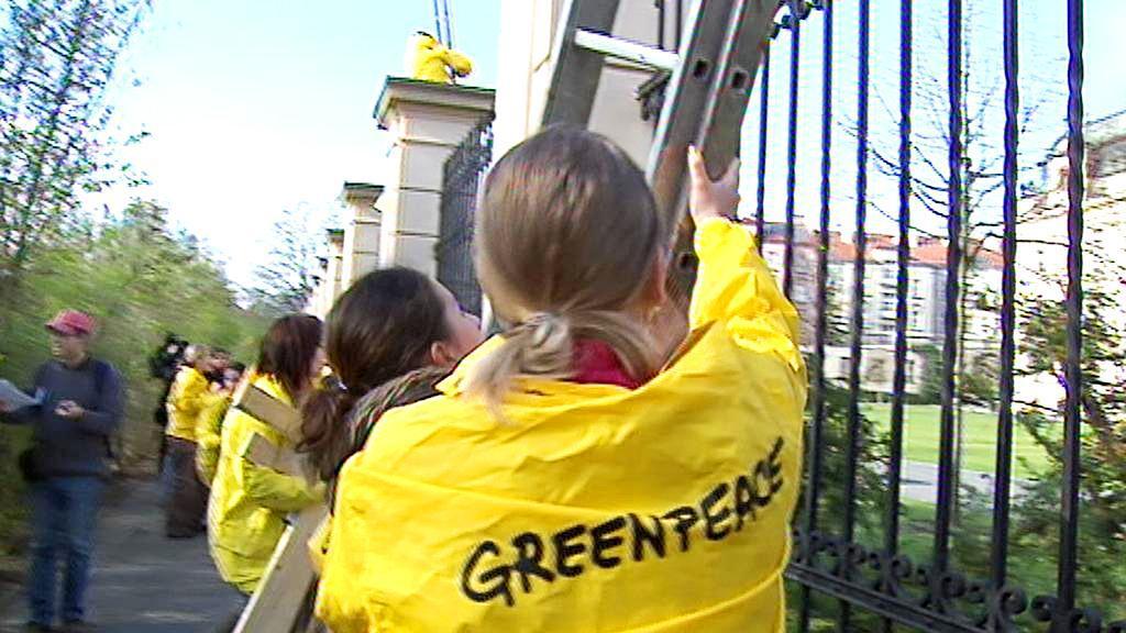 Aktivisté Greenpeace lezou přes plot do Strakovy akademie