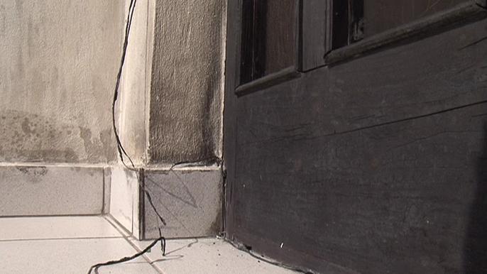 Na dveřích domu jsou stále viditelné pozůstatky požáru
