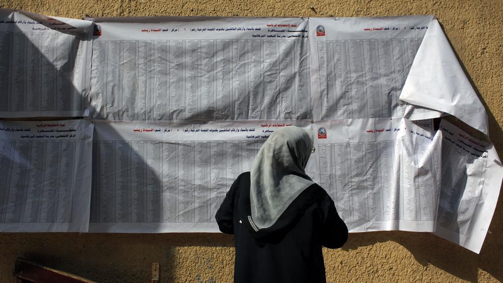 Egypťanka kontrolující volební seznam na jedné z volebních místností