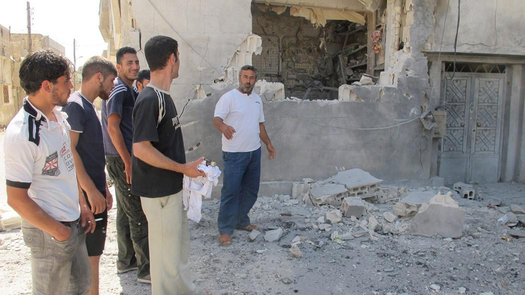 Obyvatelé města Homs stojí v troskách zbořeného obchodu