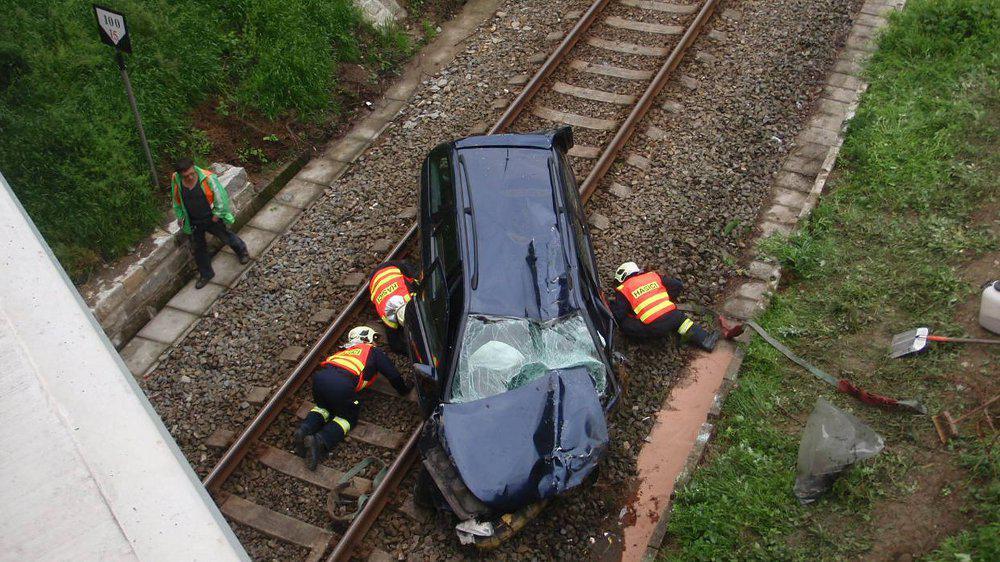 Řidič s autem spadl z mostu do kolejiště