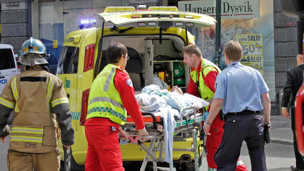 Záchranáři odvážejí muže, který se zapálil u budovy soudu v Oslu