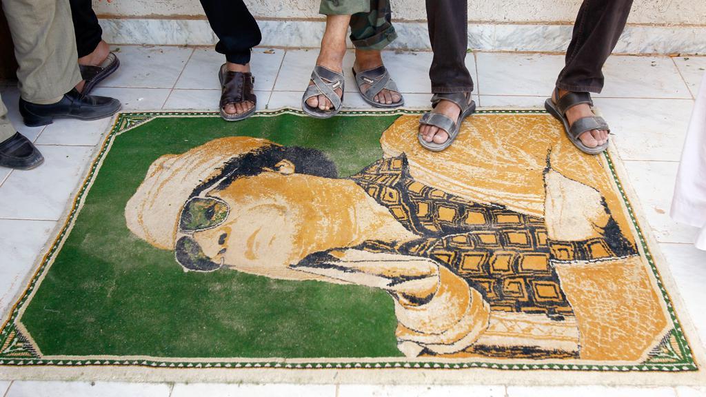 Libyjští povstalci šlapou po portrétu Muammara Kaddáfího