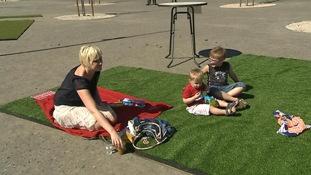 Lidé si udělali piknik na umělé trávě