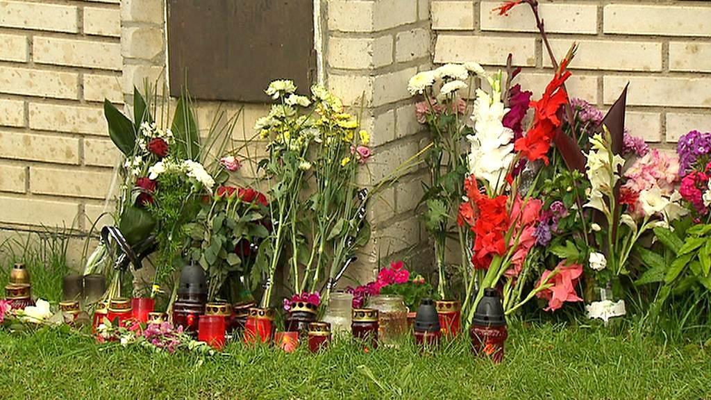 Lidé pokládají před dům obětí svíčky a květiny