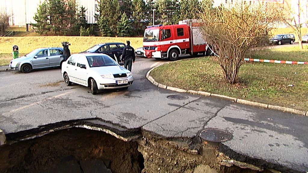 Hasiči zjišťují, zda se nemůže silnice dál propadat.