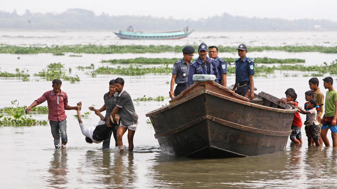Záchranáři odnášejí oběť lodního neštěstí v Bangladéši
