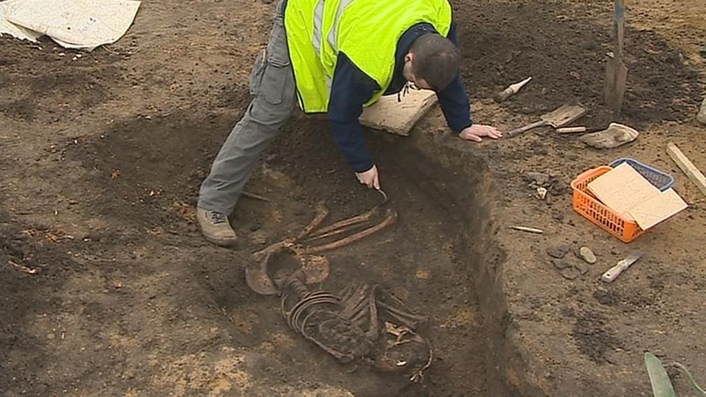 Archeolog očišťuje kostru z doby bronzové