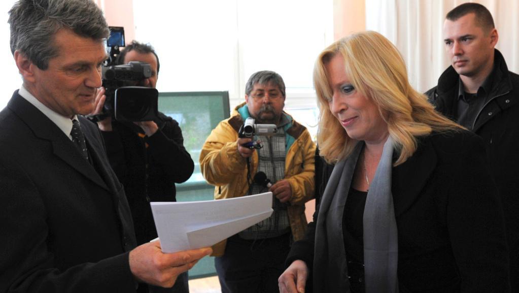 Dosluhující slovenská premiérka Iveta Radičová přebírá volební lístky od člena volební komise