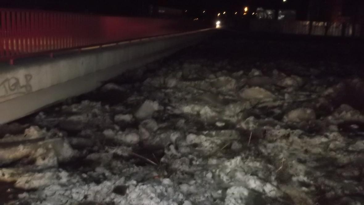 Hladina zamrzlé řeky dosáhla až k mostu