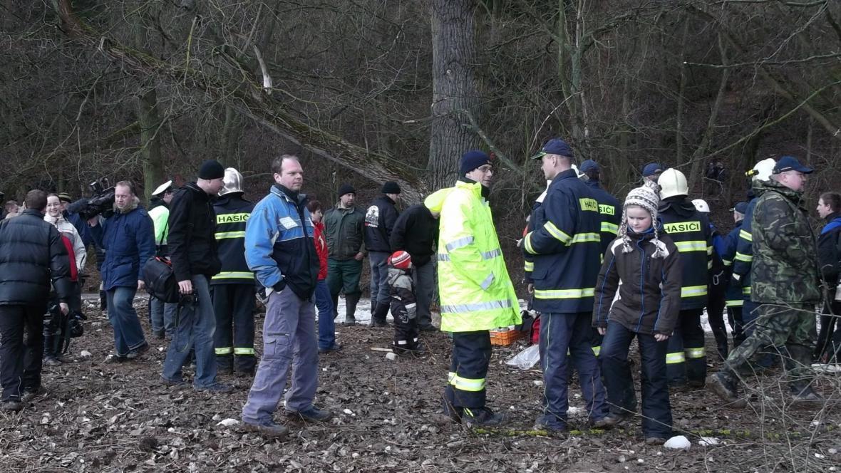 Práci hasičů a pyrotechniků přihlížejí desítky lidí