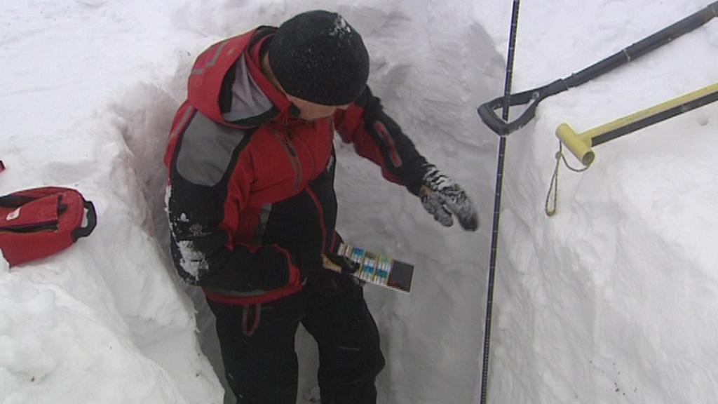 Člen horské služby měří výšku sněhu
