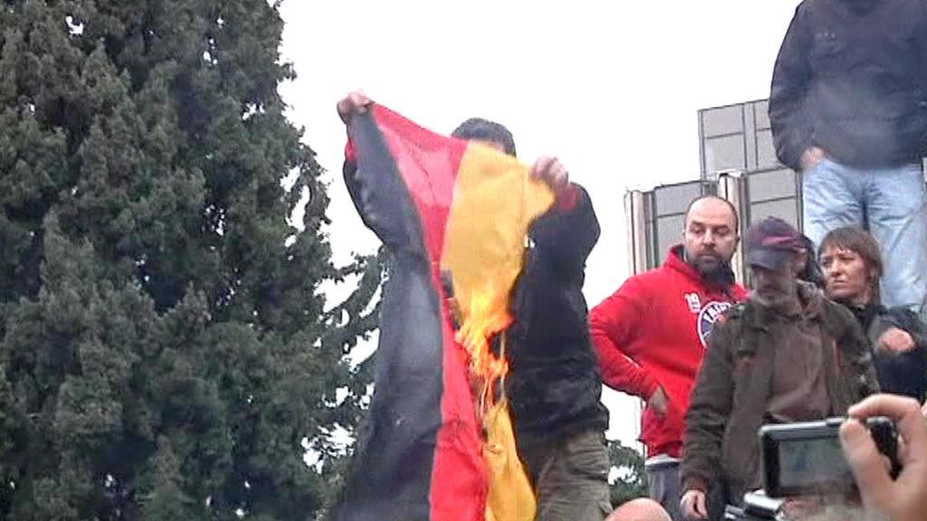 Řečtí demonstranti pálí německou vlajku