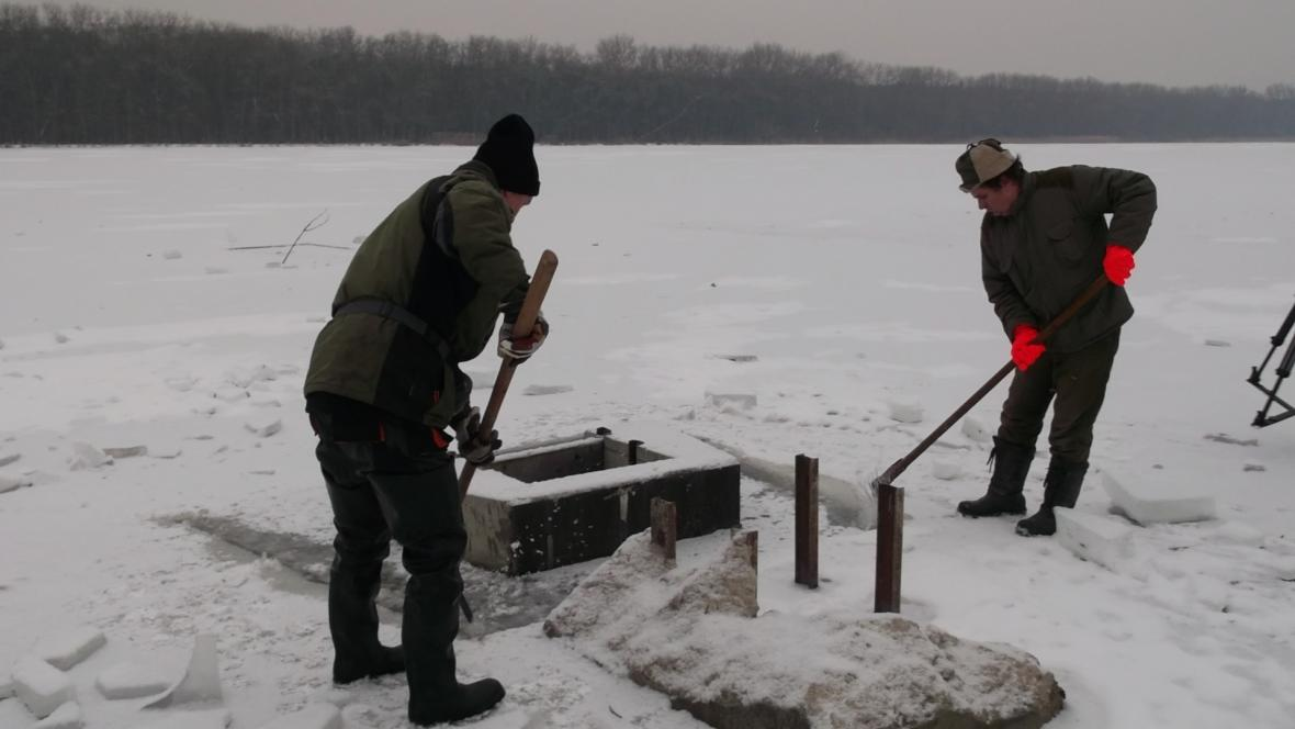 Sekání ledu na hladině rybníka