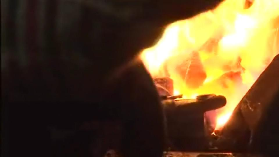 Kleště svírající železo v kovářské výhni