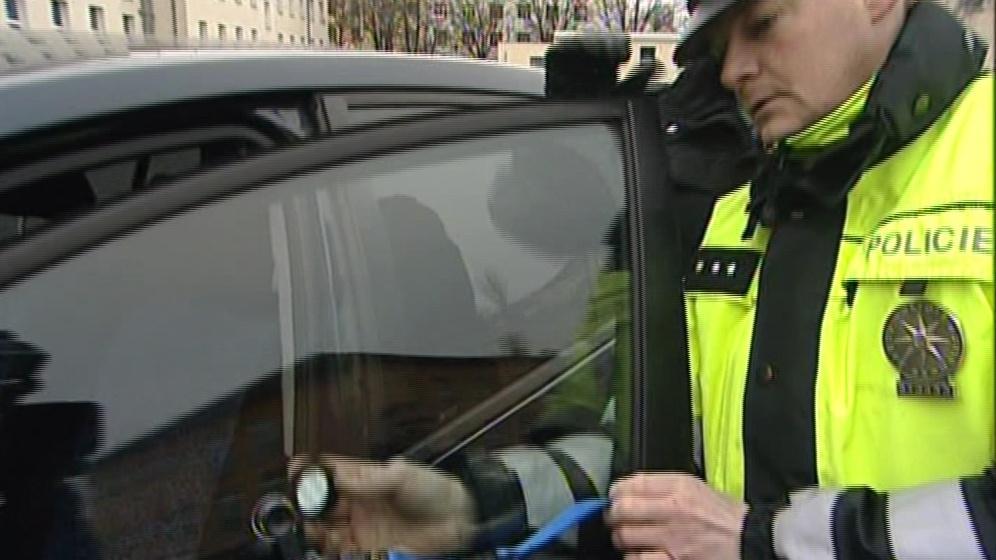 Policista měří průhlednost autoskla