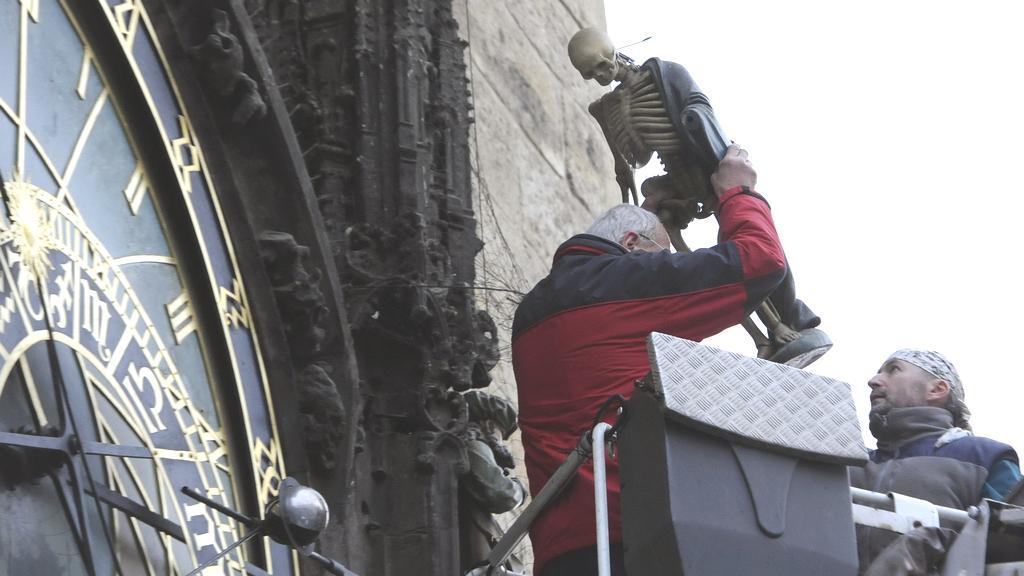 Správce snímá ze Staroměstského orloje sochu Smrtky