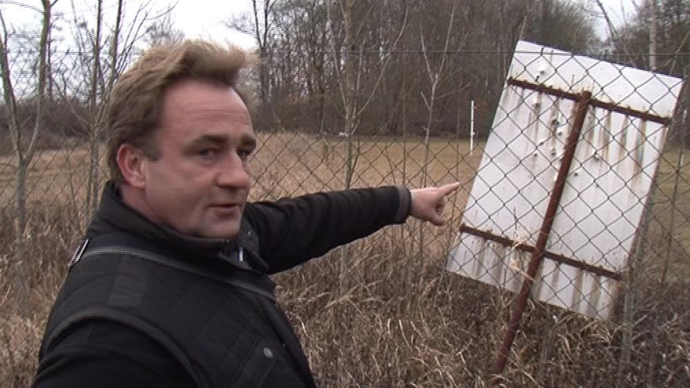 Petr Uhlíř ukazuje prostřílenou ceduli