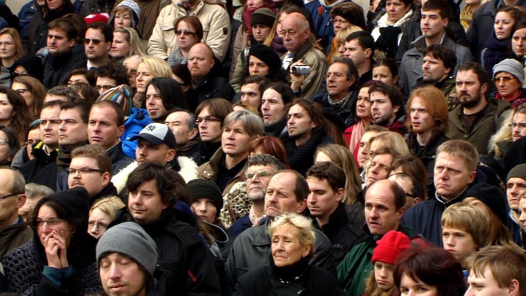Lidé na Hradčanském náměstí sledují pohřeb exprezidenta na velkoplošných obrazovkách