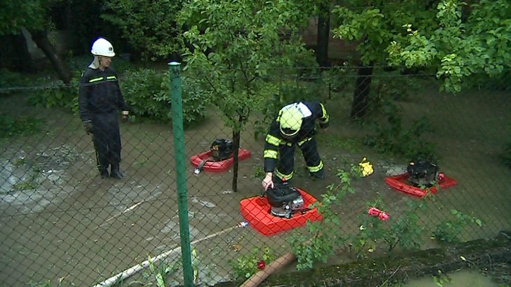 Hasiči odčerpávají vodu ze zatopené zahrady