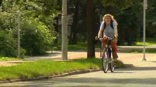 Cyklistka na silnici vedle cyklostezky