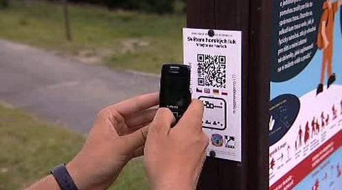 Turista fotografuje kód informační tabulky