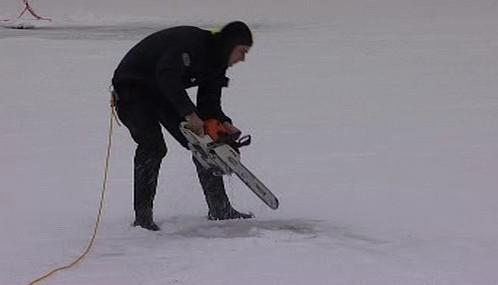 Potápěč vyřezává díru v ledu