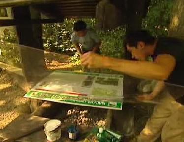Brigádníci při výměně skla u informační tabule