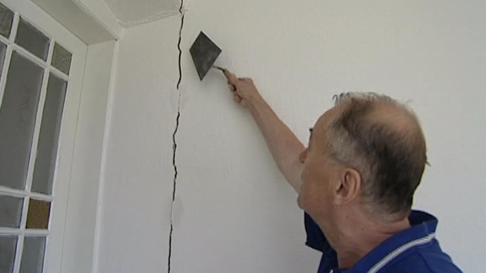 Obyvatel domu ukazuje praskliny ve zdi