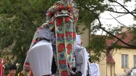 Hlucký král v přestrojení - na sobě má dámský kroj a v ústech růži