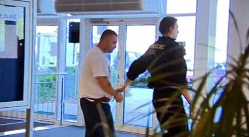 Policie odvádí jednoho ze členů gangu