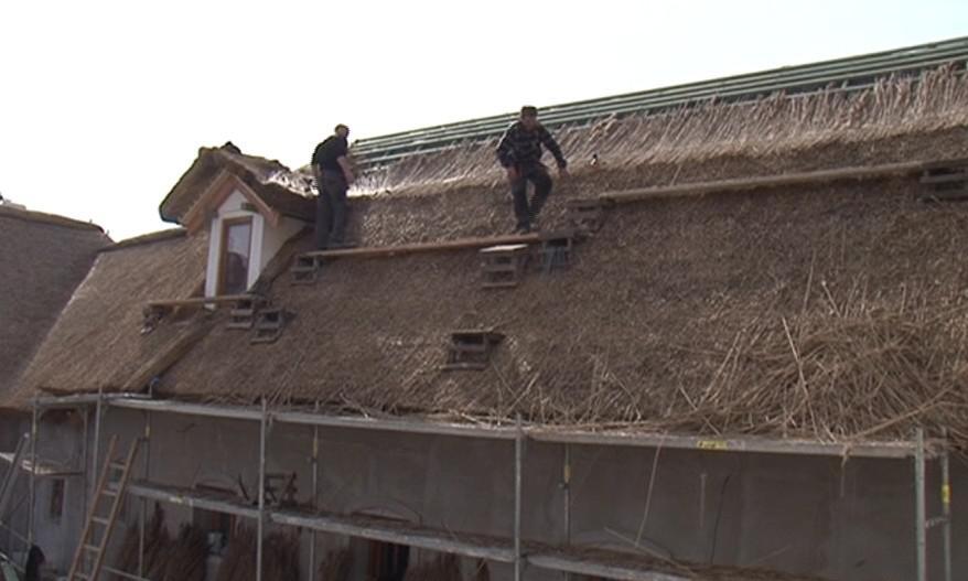 Dělníci pokrývají střechu Hanáckého statku