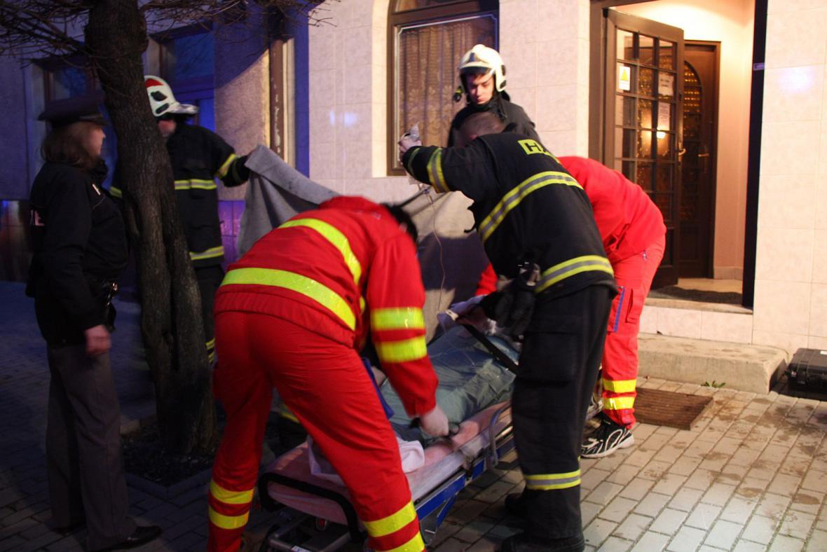 Záchranáři s hasiči nakládají popálenou seniorku