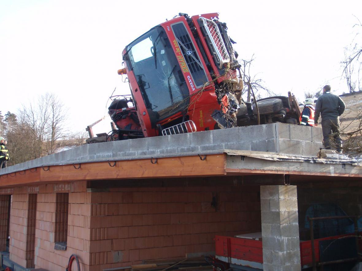 Prázdný tahač na dřevo havaroval na střechu přístavby