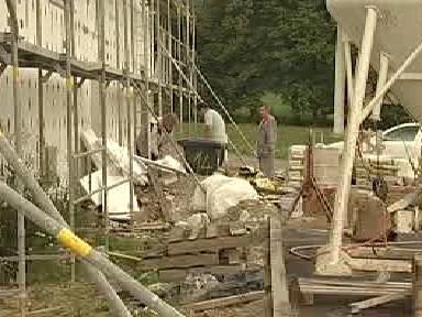 Stavební dělníci dokončují základy bytového domu