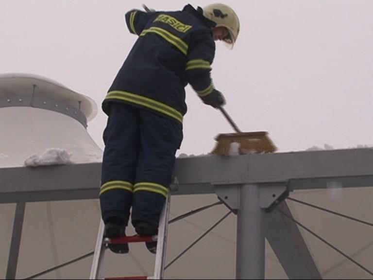 Hasiči odstraňují namrzlý sníh ze střech