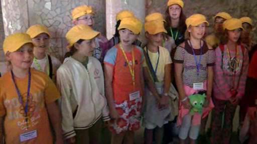 Děti zpívají v Gaudího parku v Barceloně turistům