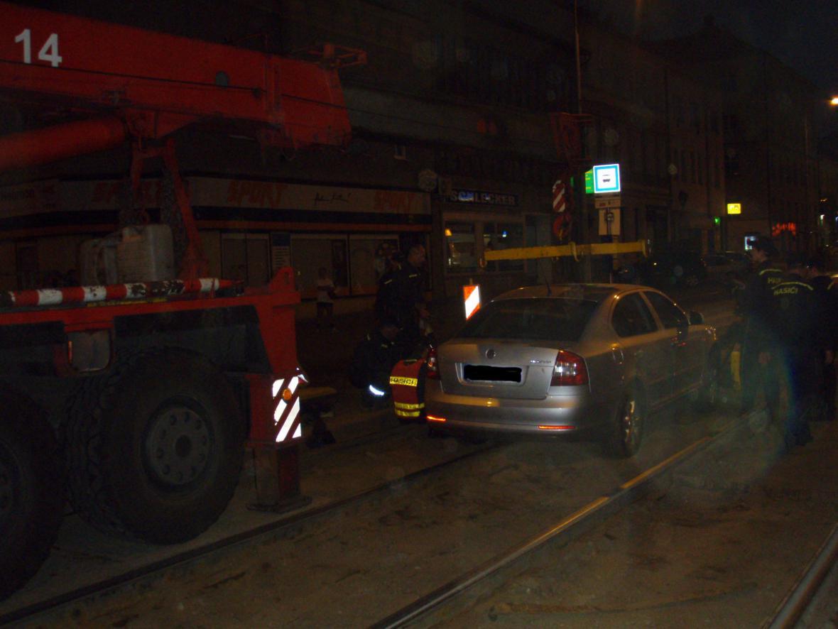 Hasiči vyprošťují auto zapadlé v kolejišti na Palackého ulici