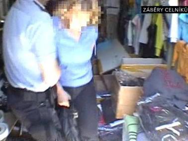 Celníci vyvádějí zamčené zákazníky z prodejních kontejnerů