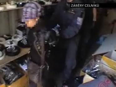 Celníci vyvádějí prodejkyni padělaného zboží