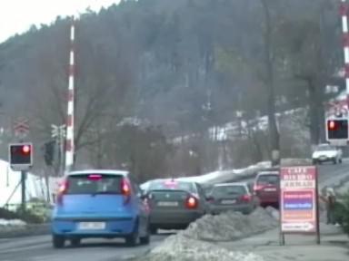 řidiči projíždějící přes koleje na červenou