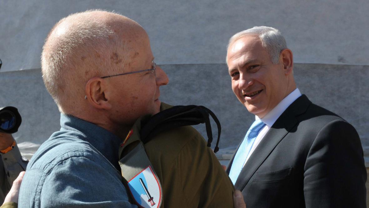 Gilad Šalit se objímá s otcem. Přihlíží Benjamin Netanjahu.
