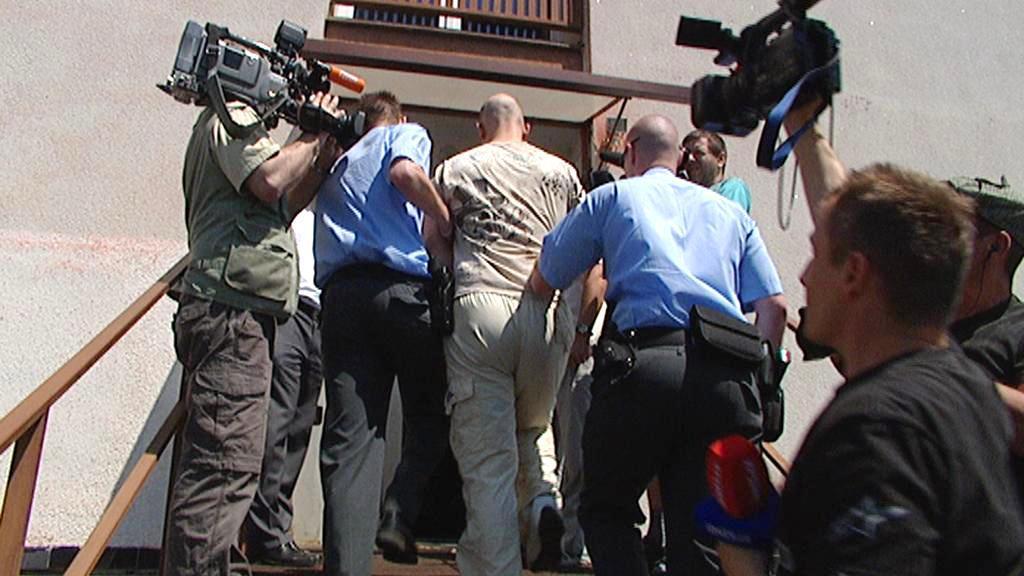 Policisté odvádějí stíhaného cizince