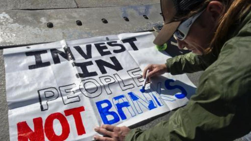 Demonstrant připravuje transparent v Mnichově