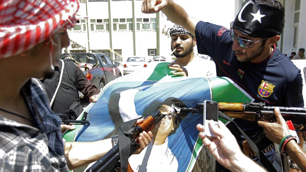 Libyjci míří na obrázek Muammara Kaddáfího