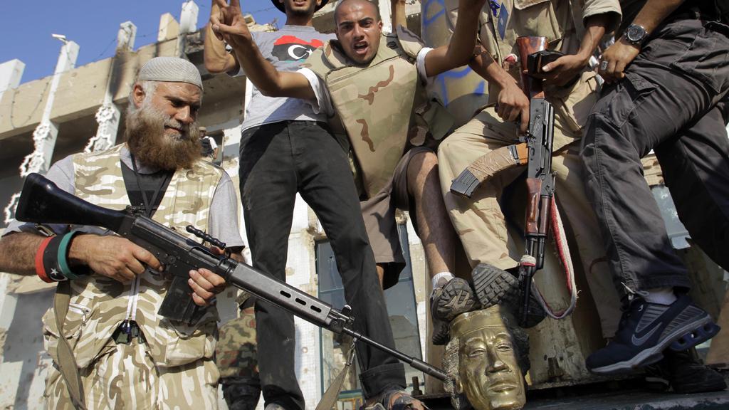 Povstalci ničí Kaddáfího sochu