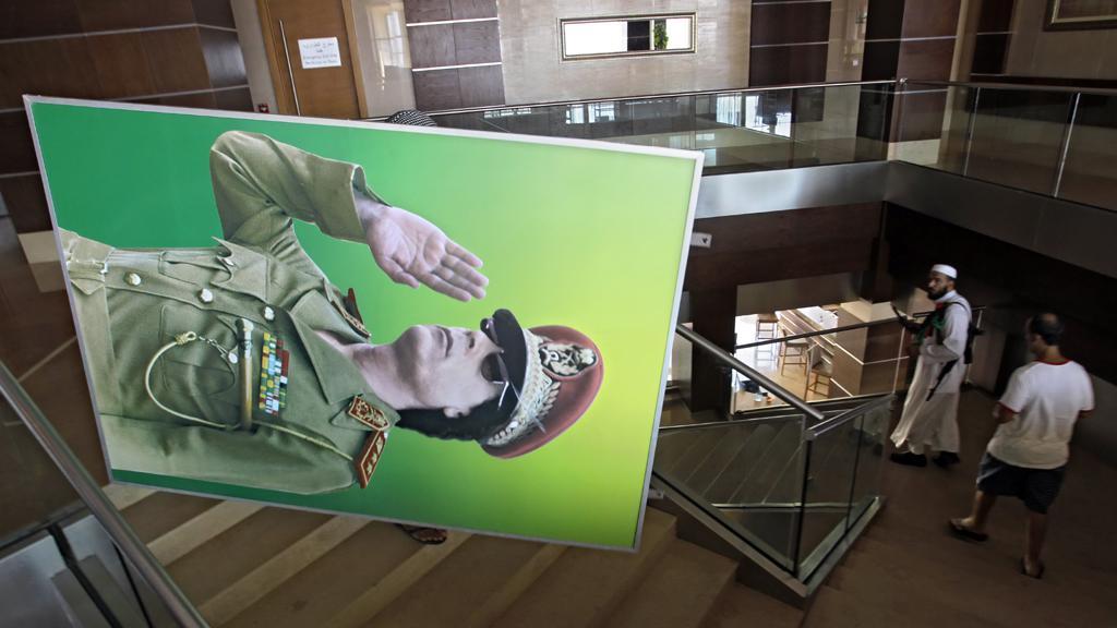Povstalci odnášejí portrét Muammara Kaddáfího z hotelu Radisson
