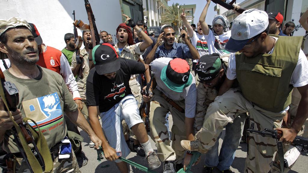 Libyjci šlapou na vlajku Kaddáfího režimu